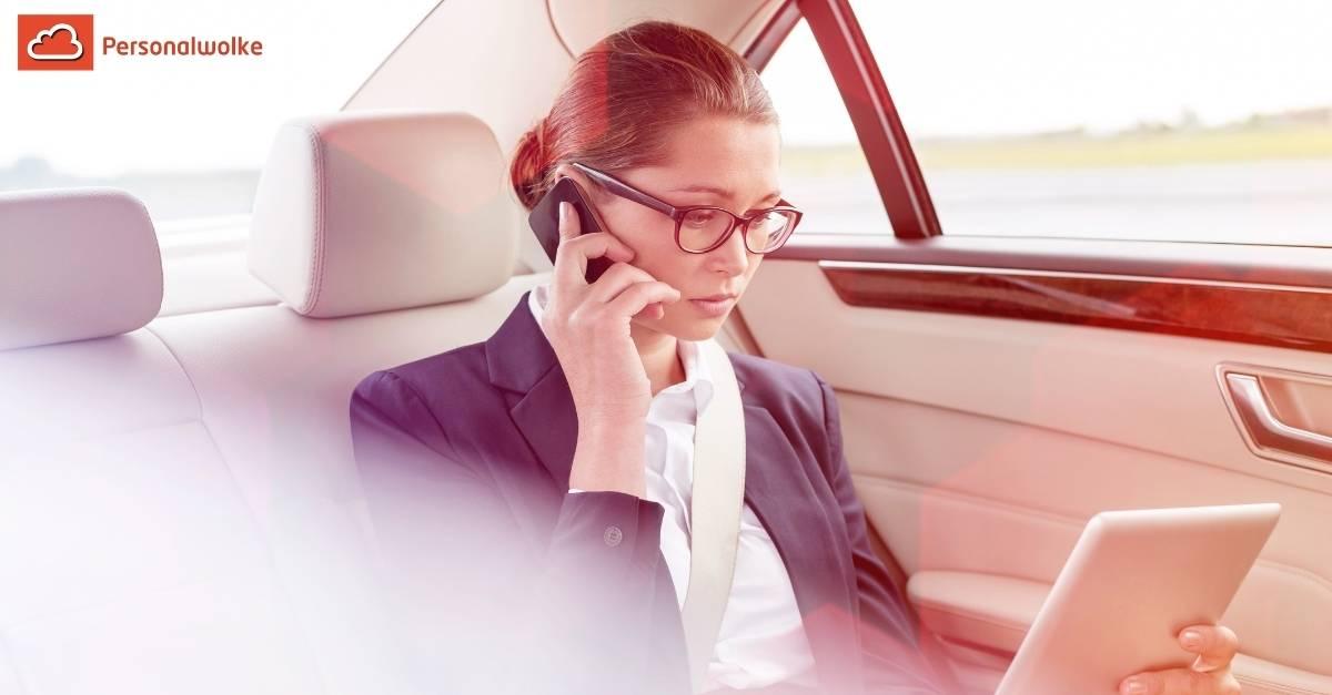 Geschäftsfreu sitzt in einem Wagen und führt ein Telefonat